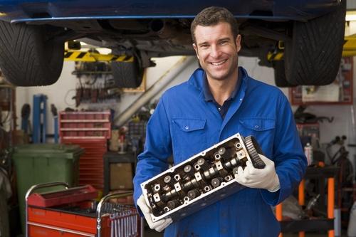 Een automonteur die een stuk van een motorblok vast heeft. Een knappe monteur die lacht naar de camera.