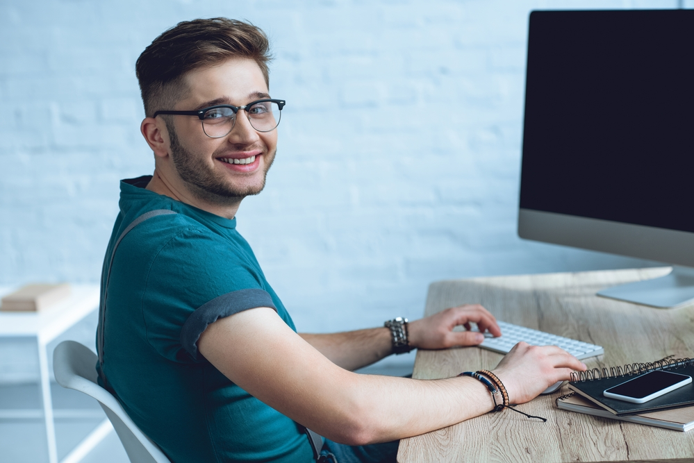 jongen werkt achter de computer op een kantoor