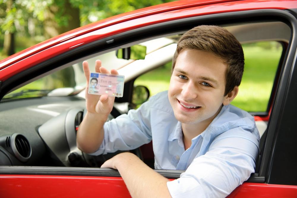 Jongere laat zijn rijbewijs zien vanuit de auto, lachend