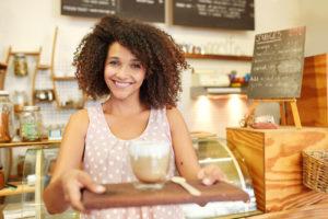 Een leuke jonge dame met afro kapsel die werkt in de bediening als serveerster