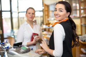 Glimlachende winkelmedewerker aan het werk in een winkel terwijl ze een klant helpt.