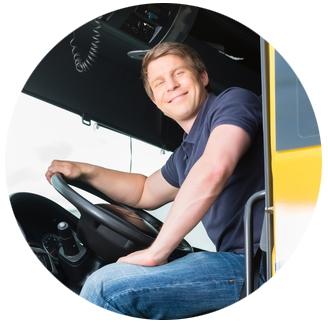 Vrachtwagenchauffeur in zijn vrachtwagen achter het stuur lachend naar de camera