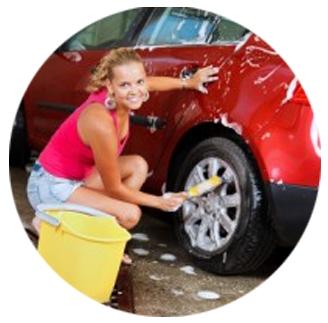 Meisje is een auto aan het wassen en lacht