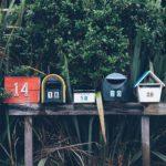 Vijf brievenbussen op een rij.