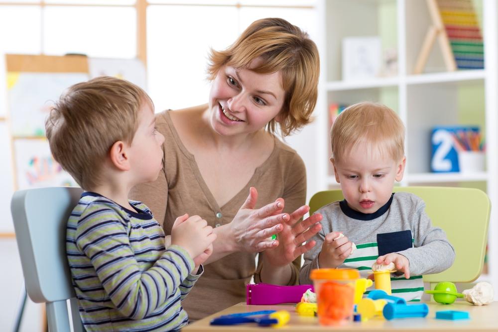 Vrouw van kinderopvang met twee kinderen