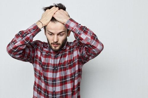 Jonge man met zijn handen in het haar van een gemiste kans, angst of wanhoop