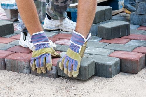 Stratenmaker maakt een straat met stenen