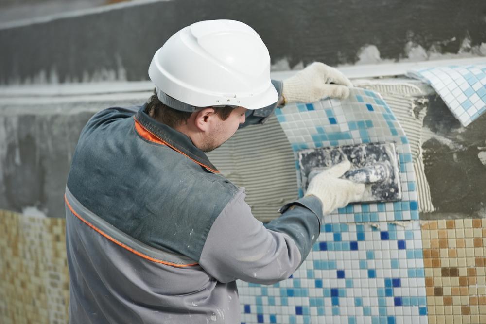 Mannelijke egelzetter met helm op plakt tegels op de muur