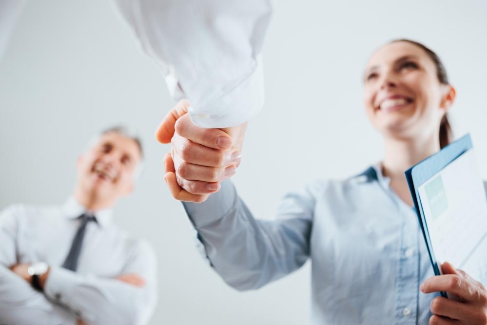 Zakenmensen die elkaar de hand schudden na een aanname van een sollicitant