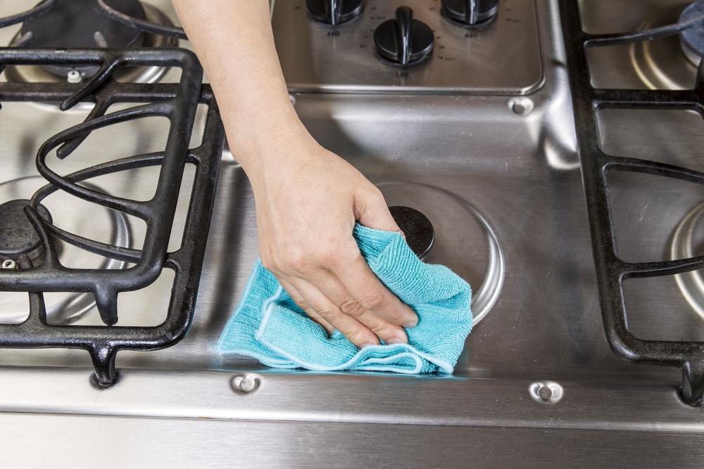 Iemand neemt een kookstel af met een blauwe doek